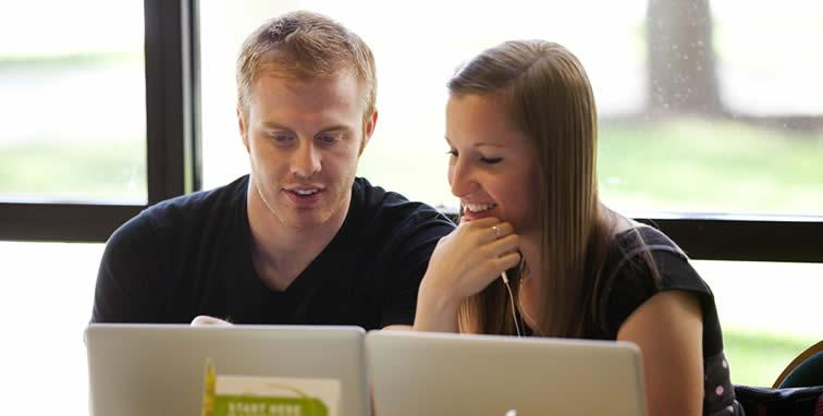 two students on a laptop studing