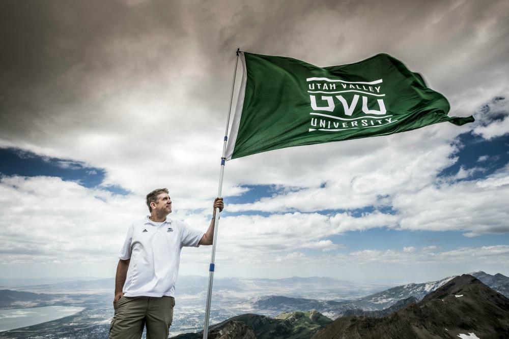The UVU President hold a UVU flag.