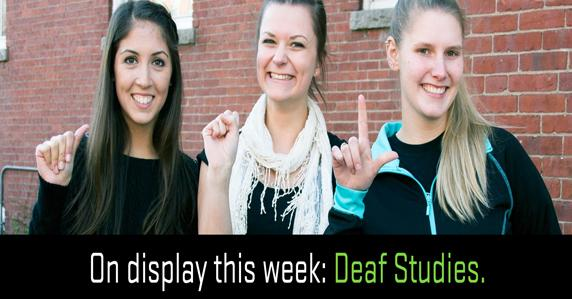 3 girls signing. The book display for the week is about deaf studies.