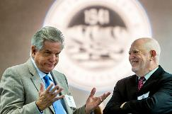 two board members talk in front of the UVU seal displayed on a back wall