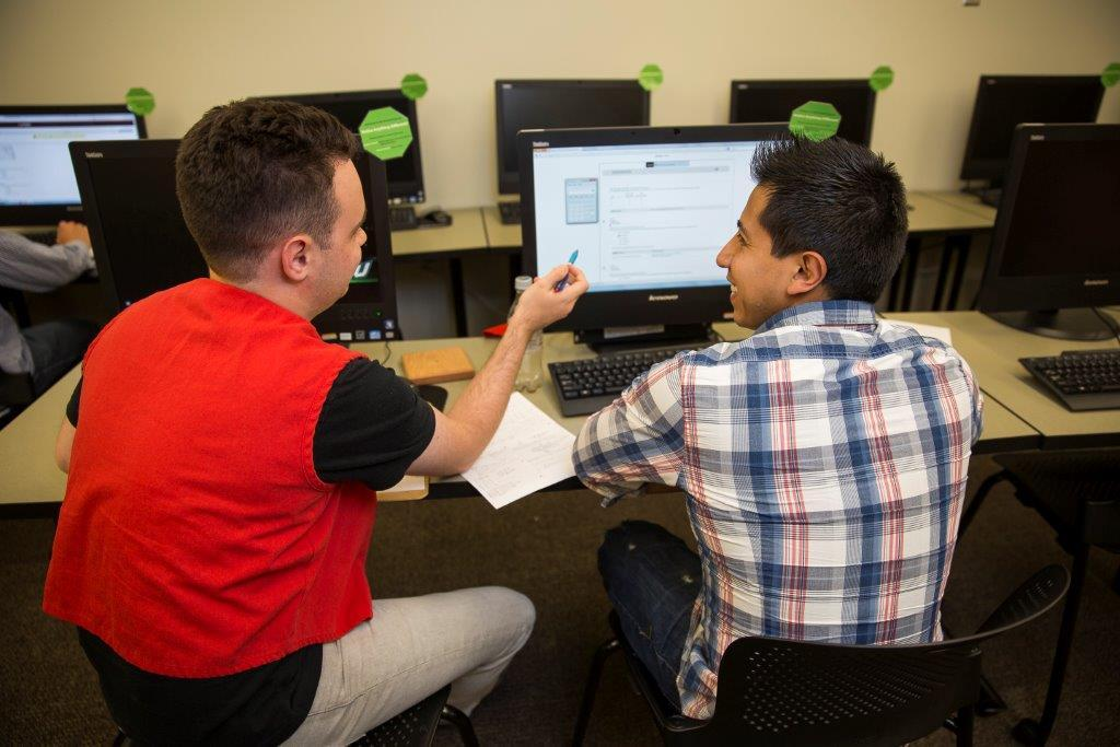Tutor help a student on a computer