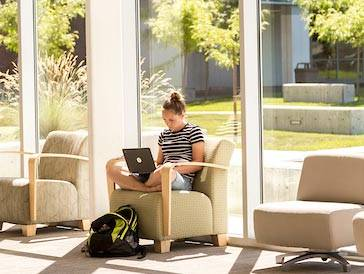 Student sitting in chair studying with a laptop