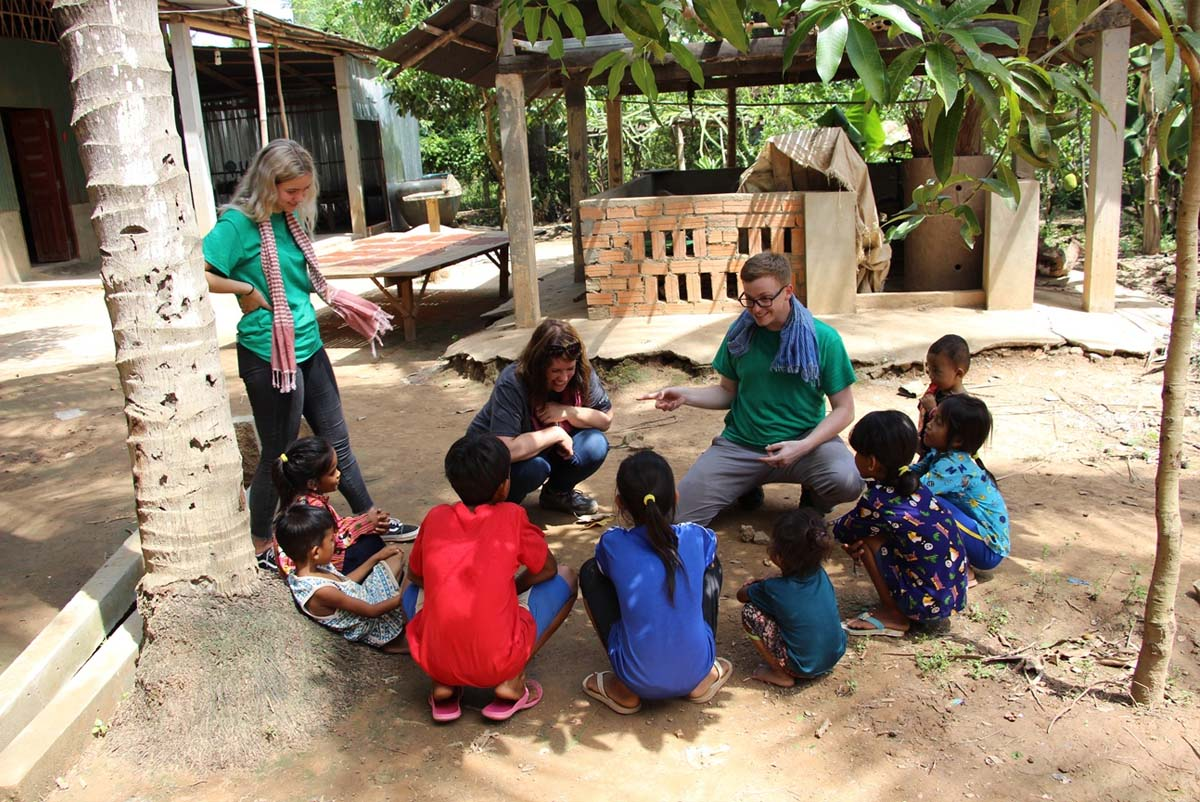 UVU students teach public health on dirt Cambodian streets to a circle of small children.
