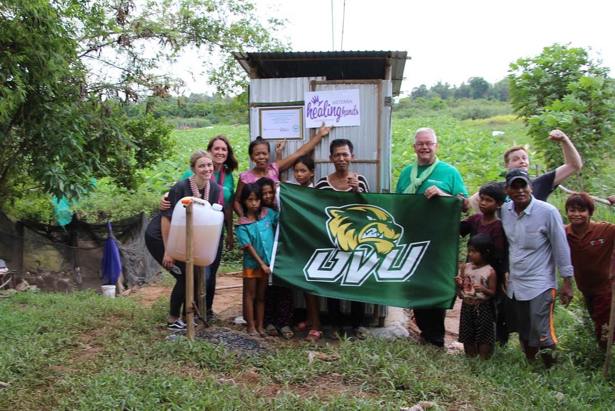 Professor Barthel and team pose with UVU flag in front of a new latrine.
