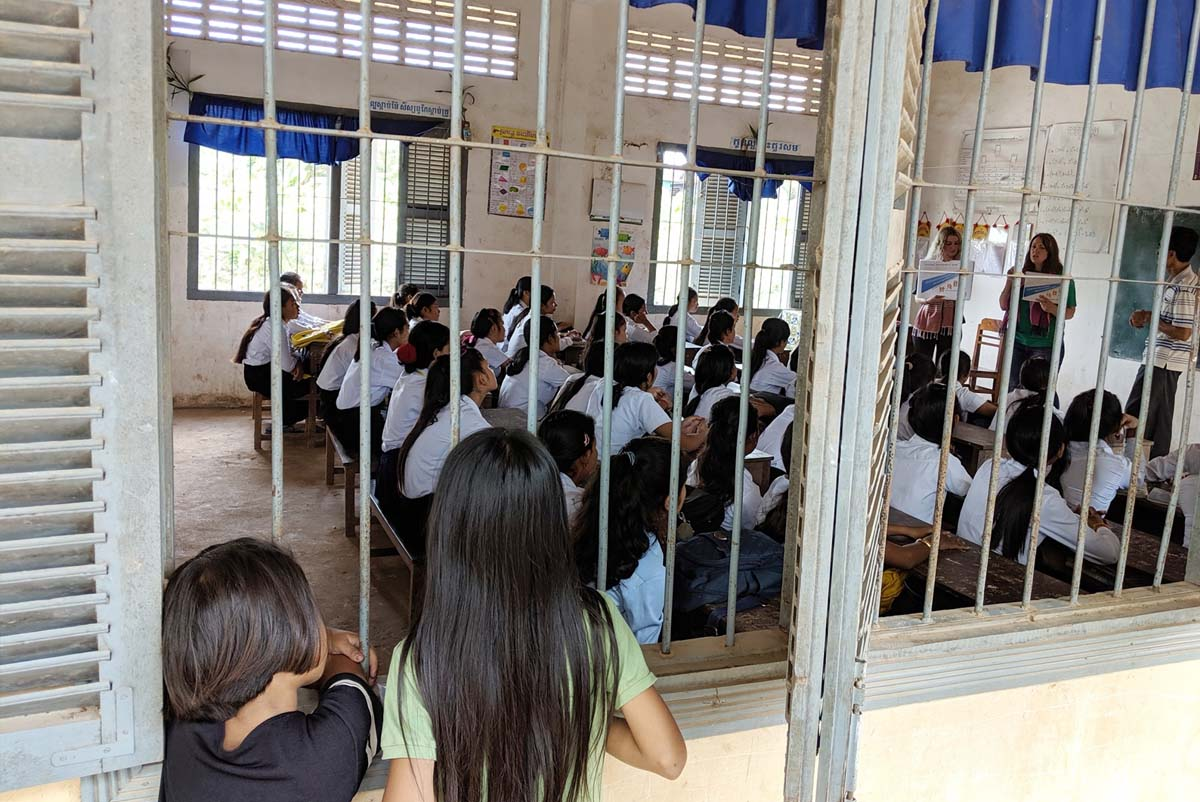 Two girls lean on the barred windows of the primary Cambodian school to lisen in on Professor Barthel's lecture.