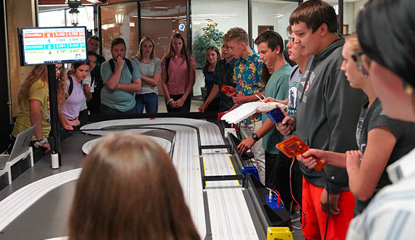 High school students take a break and race on a miniturate remote control car track.