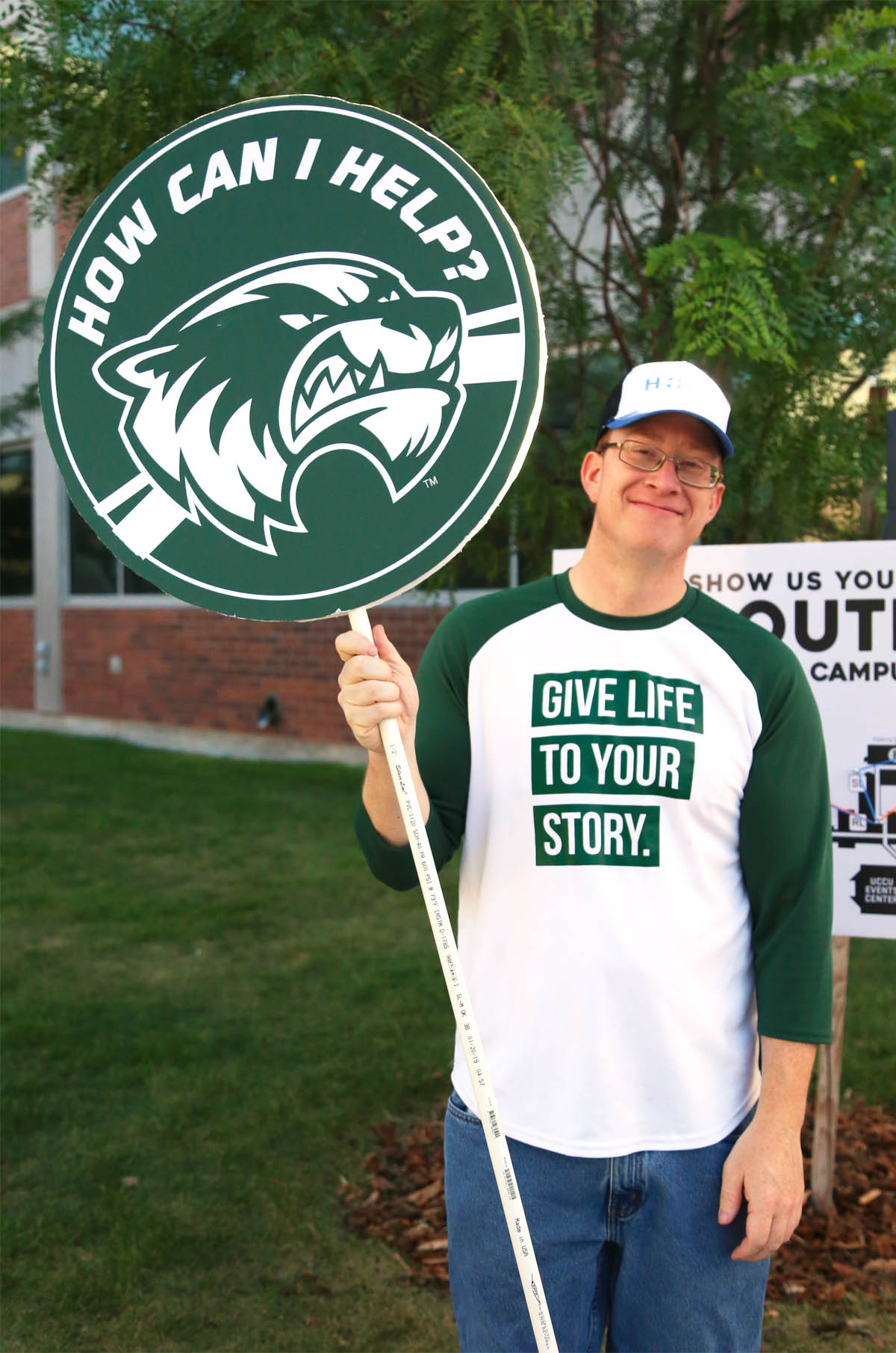 "Student in UVU apparel holding a ""how can I help?"" sign."