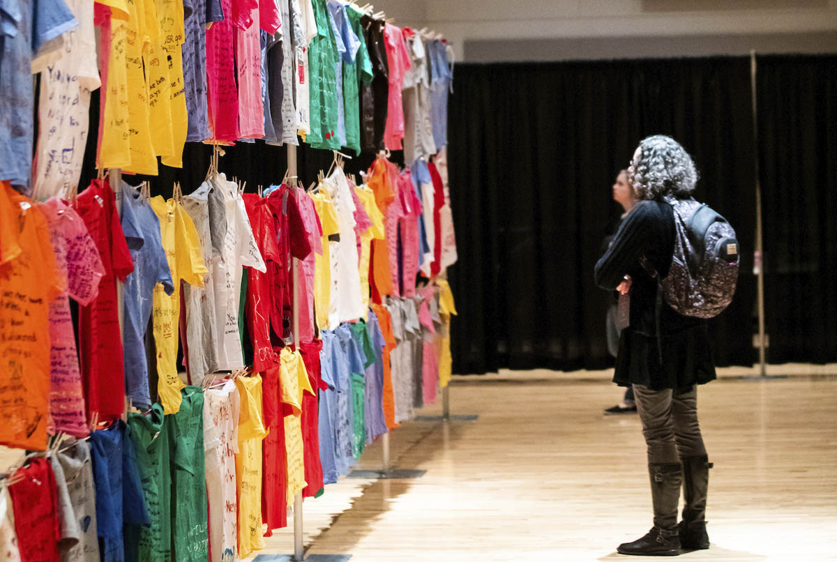 Students read a wall of colorful t-shirts decorated by survivors of domestic abuse at the Clothesline Project at Utah Valley University.