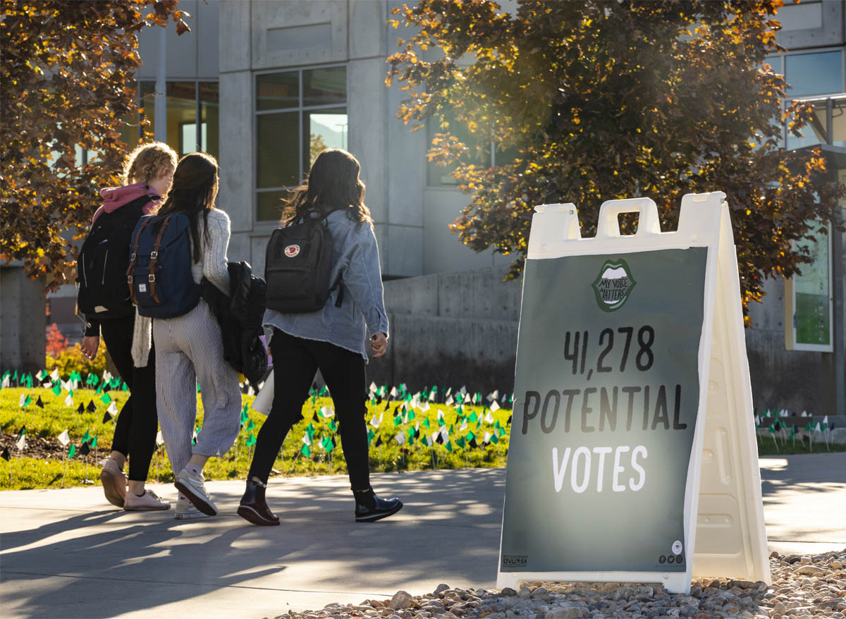 Students pass hundreds of small green, white, and black flags planted in Utah Valley University's lawn in front of the library.