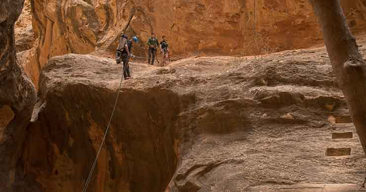 Three people rappelling down a cliff.