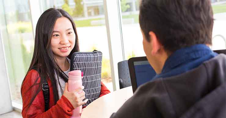 Female student talking with a male employee.  Female student is asian and is smiling about the covnerstaion.