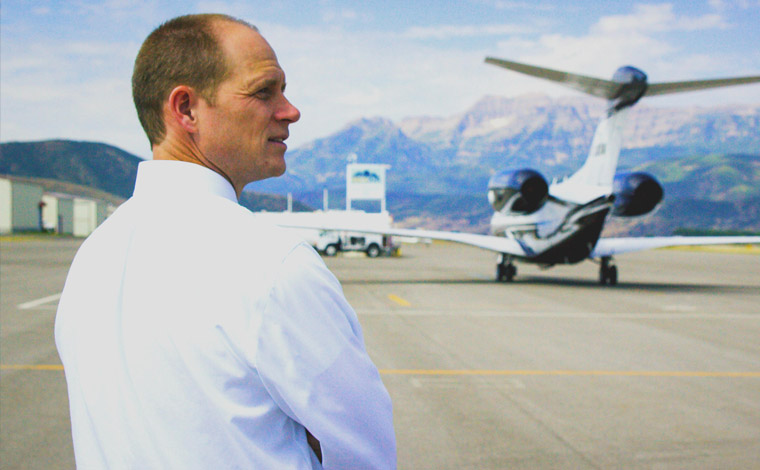 Person standing in foreground with small airplane in the background.