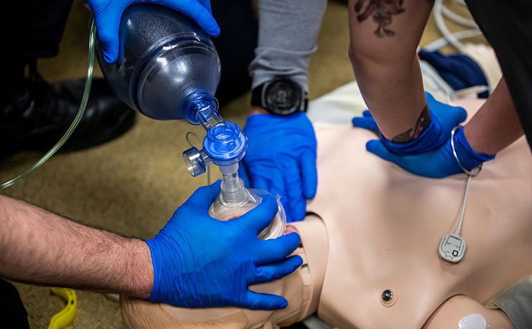 People performing CPR on a CPR dummy.