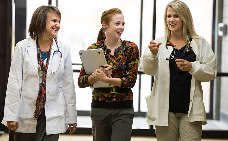 Group of women wearing lab coats and stethoscopes.