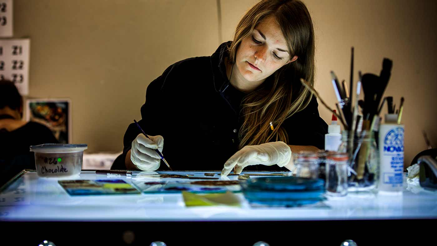 Girl working on a piece of glass for Roots of knowledge.