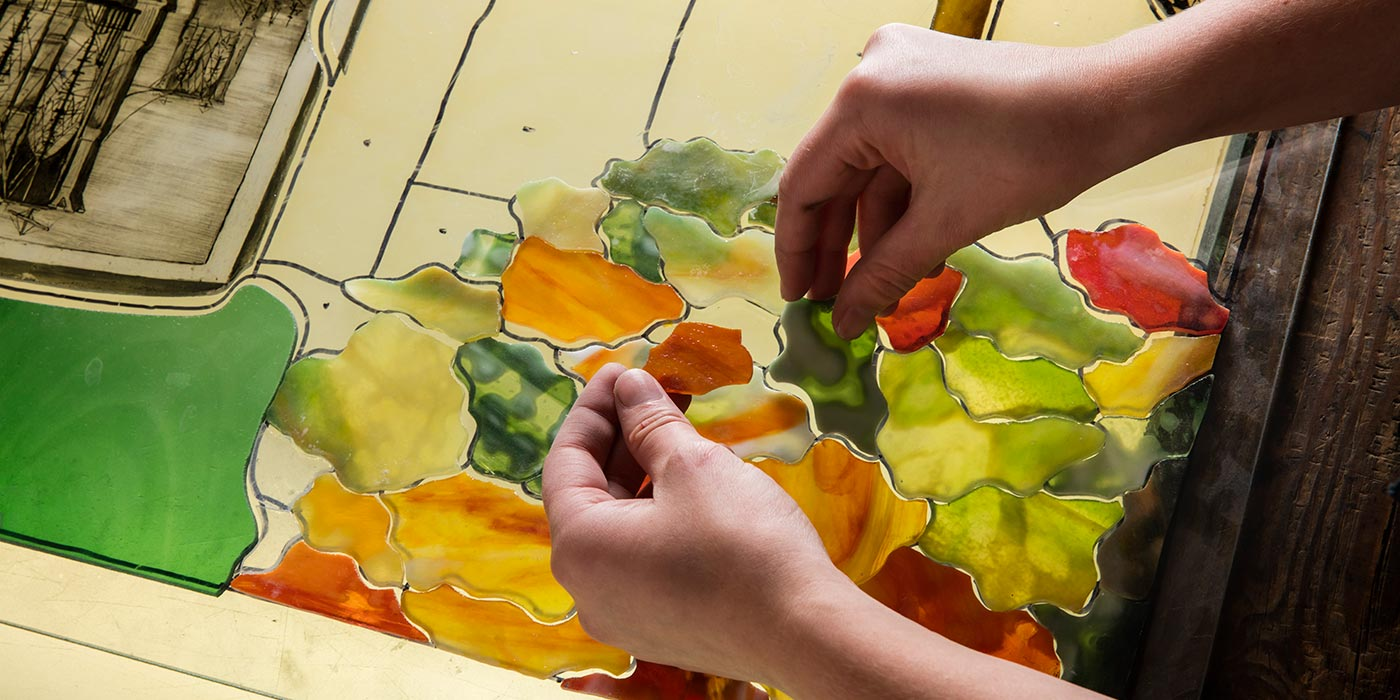 Cutting glass by hand.