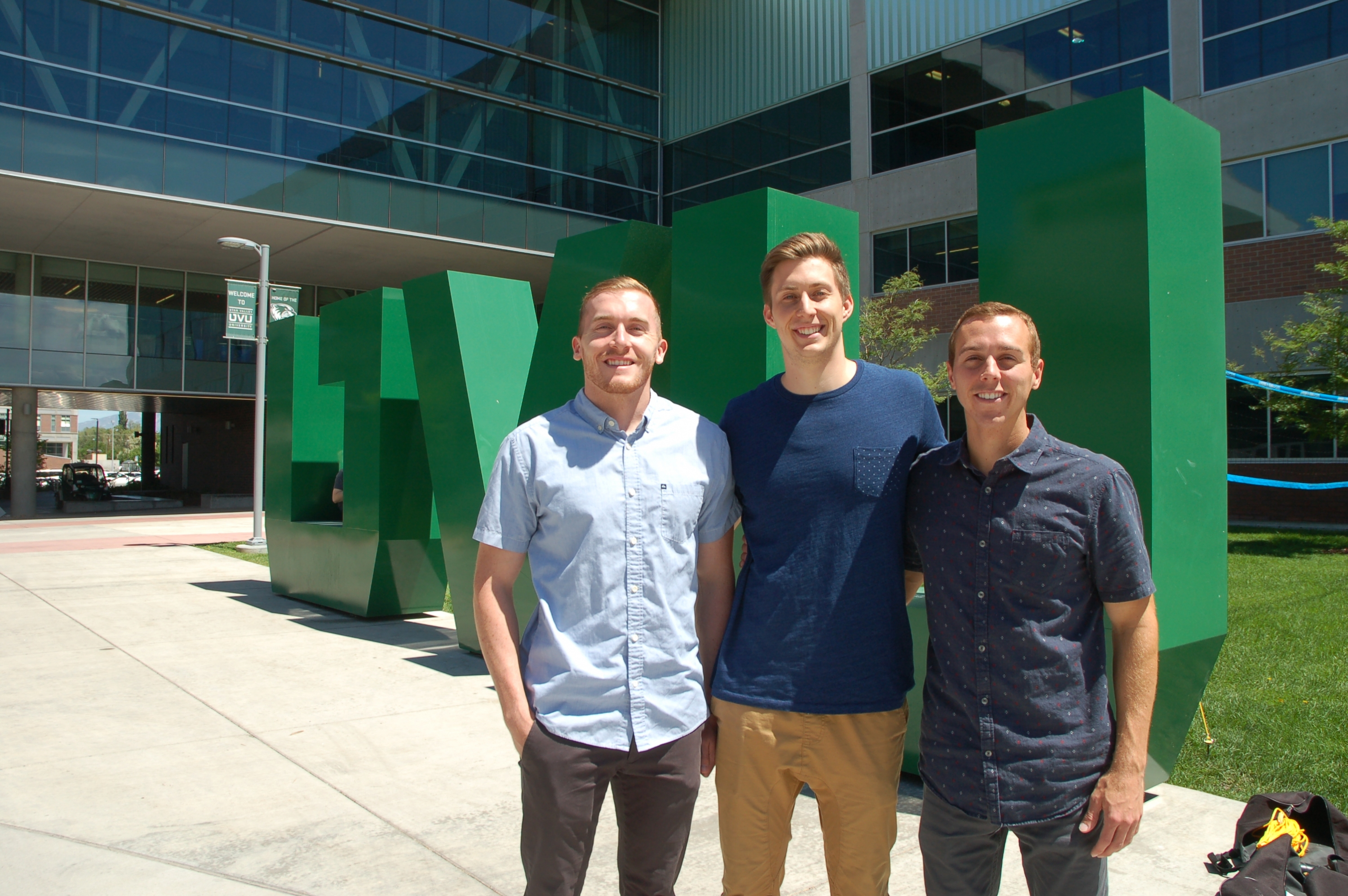 Three UVU students in front of giant green U.V.U. letters