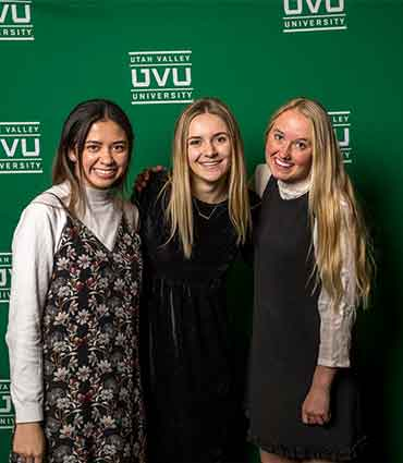 three female students standing in front of a wall covered with the uvu logo