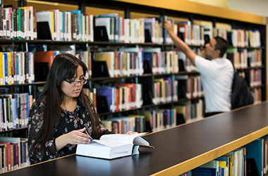 Student looking at large book at the library