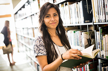 Student smiling with a library book