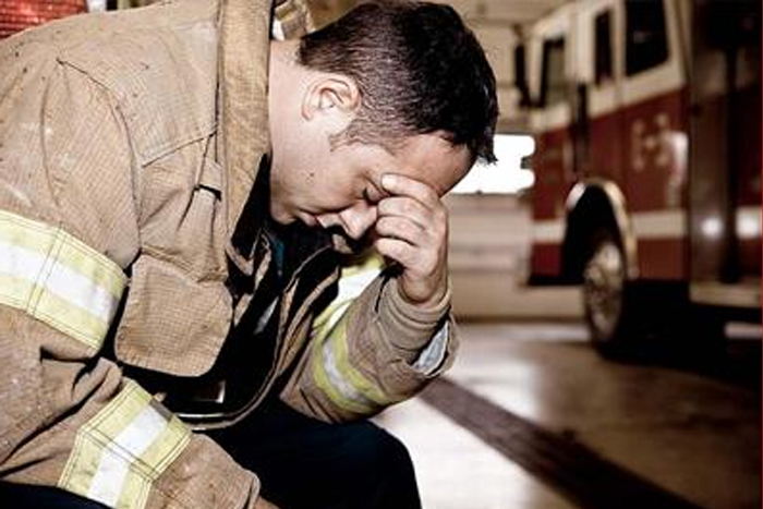Firefighter after a fire in the firehouse sitting with his head on his hand