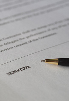 Pen and paper contract with a line for a signature