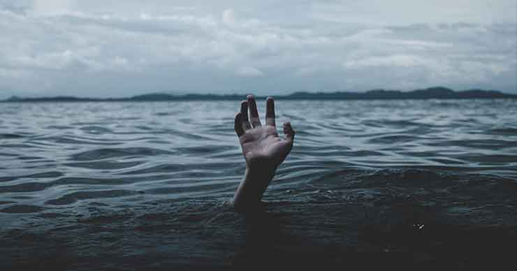 A hand sticking up out of a body of water, as if the person is drowning.