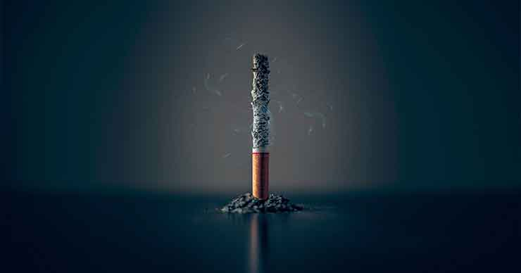 A cigarette standing upright, burning with ash falling on the table.