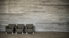 three green soft chairs in front of a stone gray wall.