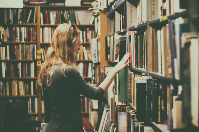 woman looking for book in library